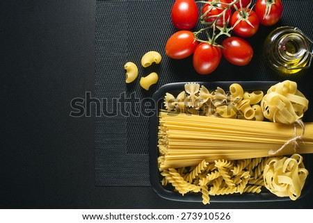 Raw mixed pasta on black background overhead shoot