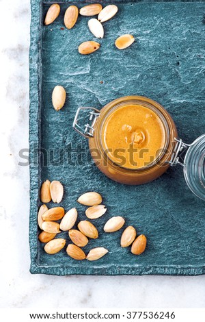 Raw Organic Almond Butter with a few peeled almond on a quartz stone Background. Vertical photo of homemade natural almond butter in a glass jar. Pastel colors. View from above. - stock photo