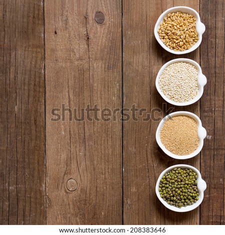 Raw Organic Amaranth and quinoa grains, wheat and mung beans in small bowls - stock photo