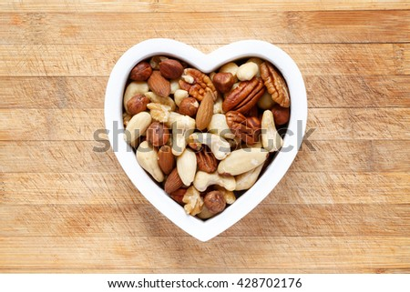 Raw organic nuts in heart shaped bowl