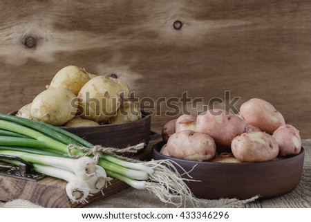 Raw organic potatoes and spring green onion on rustic wooden table - stock photo