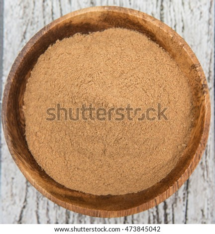 Raw organic super fruit camu camu powder in wooden bowl over wooden background
