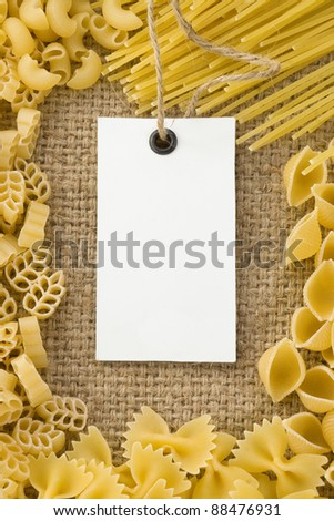 raw pasta and price tag on sack hessian as background - stock photo