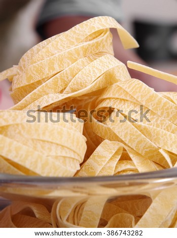 Raw pasta in a glass bowl is ready to cook - stock photo