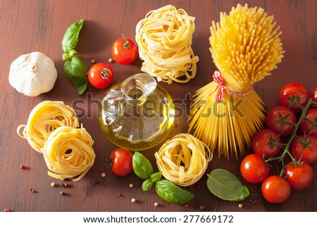 raw pasta olive oil tomatoes. italian cooking in rustic kitchen - stock photo