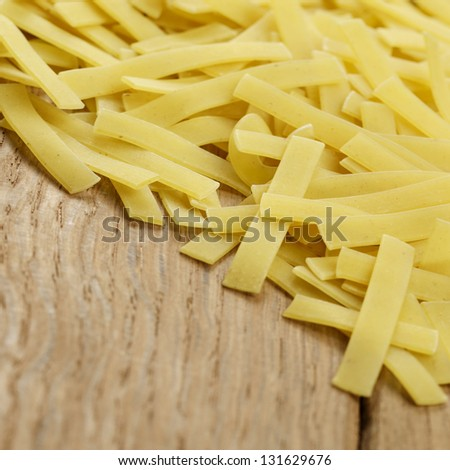 Raw pasta on the wooden table with copy-space
