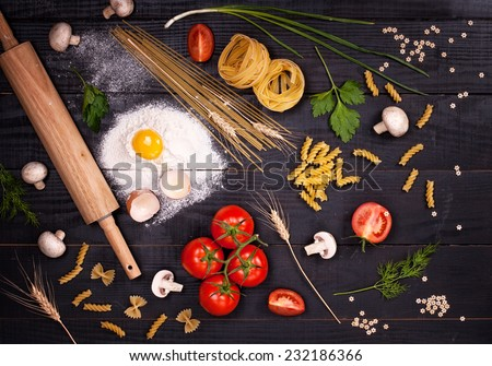 Raw pasta, tomatoes,mushrooms, flour and eggs on black wooden table background, top view - stock photo