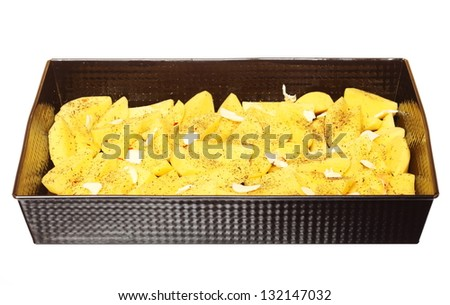 Raw peeled potatoes in tray with spices, butter slices ready to be roasted white background - stock photo