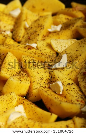 Raw peeled potatoes with spices, butter slices ready to be roasted as background