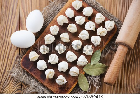 Raw pelmeni, eggs, bay leaves and rolling pin, above view