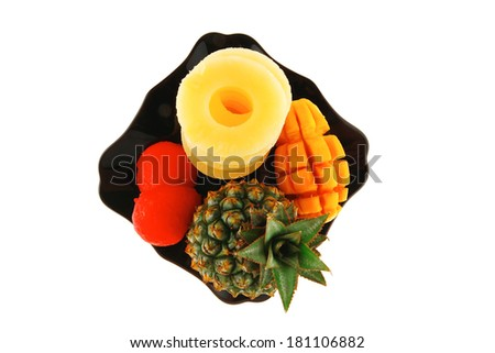 raw pineapple on black plate isolated over white background - stock photo