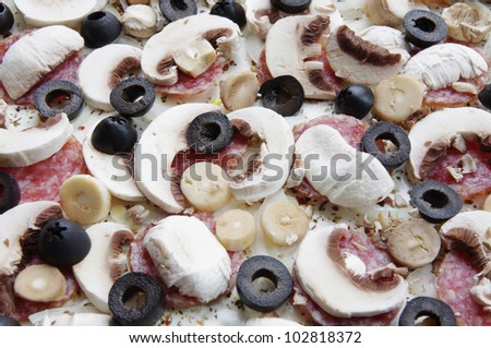 raw pizza with salami, olives and mushrooms