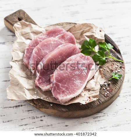 Raw pork chops on a rustic wooden cutting board on a wooden background - stock photo