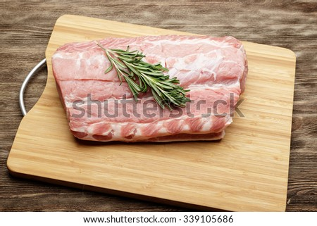 Raw pork fillet with rosemary ready for cooking - stock photo