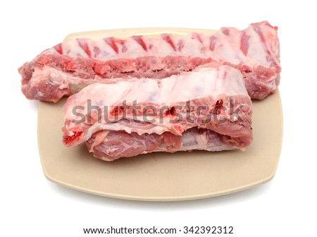 raw pork ribs on plate isolated on white background