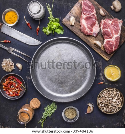 raw pork steak with herbs, mushrooms and garlic around the pan place for text,frame on wooden rustic background top view - stock photo