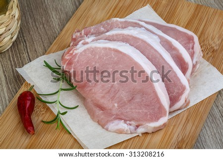 Raw pork steak with rosemary branch and hot pepper