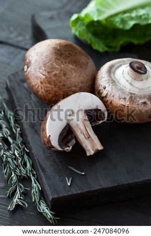 Raw portobello mushrooms with rosemary on cutting board on dark wooden table - stock photo