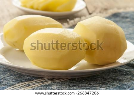 raw potato on kitchen table - stock photo