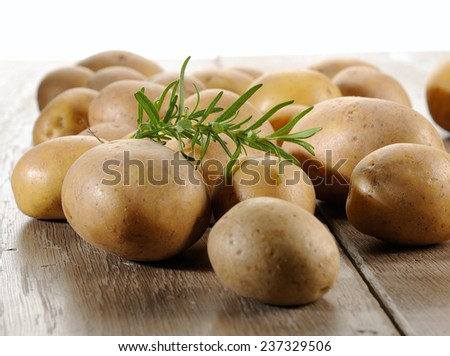 Raw potatoes  and rosemary background  - stock photo