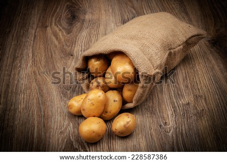 Raw potatoes in the sack on wooden background - stock photo