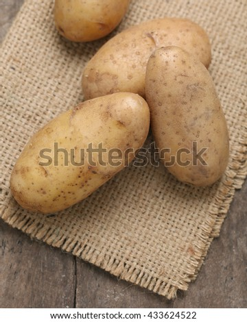 Raw potatoes on wooden background. Organic potatoes. - stock photo