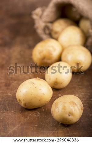 Raw potatoes out of a sack on rustic wood table  - stock photo