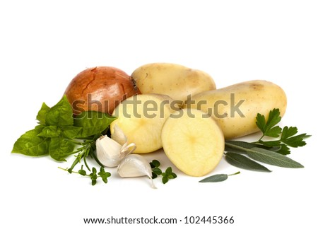 Raw potatoes, whole and cut, with brown onion, garlic cloves and herbs, isolated on white background.