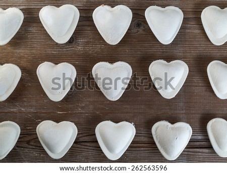 Raw ravioli in the form of hearts on a dark wooden background closeup. Top view. - stock photo
