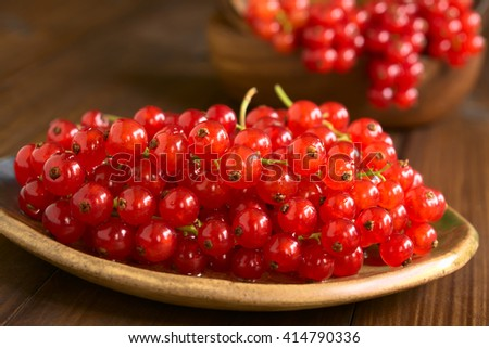 Raw red currants (lat. Ribes rubrum) on plate, photographed on dark wood with natural light (Selective Focus, Focus one third into the redcurrants)