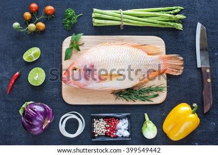Raw red fish (Nile tilapia), herbs and spices, fresh vegetables (bell pepper, asparagus, cherry tomato, eggplant) on a dark wooden board. Diet / healthy food concept. Cooking background. - stock photo