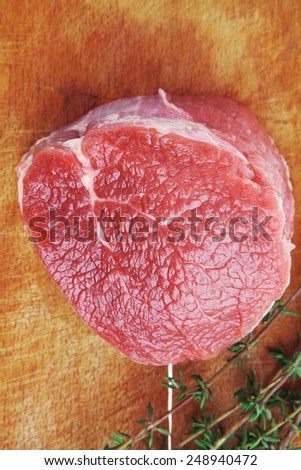 raw red meat : fresh beef single fillet chop with thyme on wooden plate . isolated over white background - stock photo