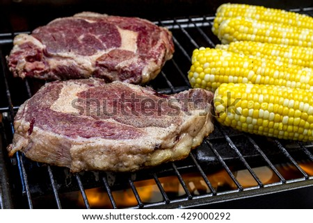 Raw ribeye steaks and corn on the cob cooking over flames on grill