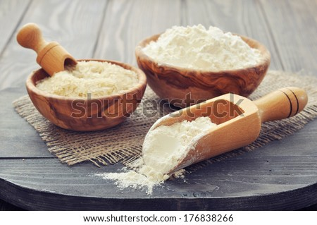 Raw rice and flour in bowls with scoop on wooden background - stock photo