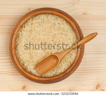 Raw rice in the bamboo bowl over wooden surface - stock photo