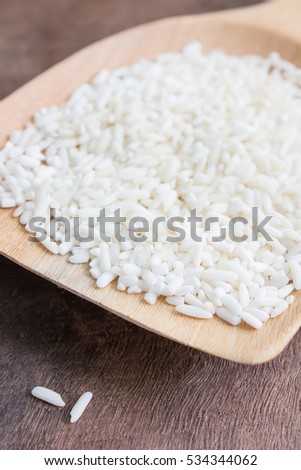 Raw rice in wooden spoon