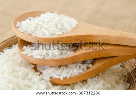 Raw rice jasmine in Thailand on wooden spoon on sack background. - stock photo