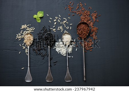 Raw rice kernels of different types over black wooden background, above view - stock photo