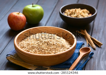 Raw rolled oats in wooden bowl with apples, cinnamon sticks and a bowl of fruit crumble in the back, photographed on dark wood with natural light (Selective Focus, Focus one third into the oats) - stock photo