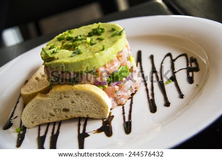 Raw salmon chopped and mixed with pepper and onion sour cream, Avocado cream and chives as garnish