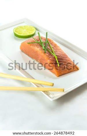 Raw salmon fillet steak garnished with chives and a slice of lime on white plate - stock photo