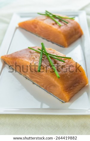 Raw salmon fillet steaks garnished with chives and a slice of lime on white plate - stock photo