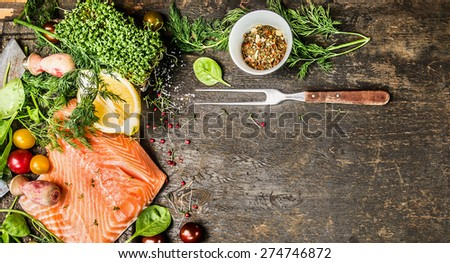 Raw salmon fillet with fresh seasoning, spices and fork on rustic wooden background, top view, banner for website with cooking concept - stock photo
