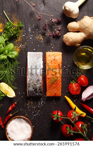 Raw salmon fillets surrounded by savory ingredients including spicy root ginger, fresh herbs, tomato, chili pepper, garlic and olive oil for a gourmet dinner recipe - stock photo