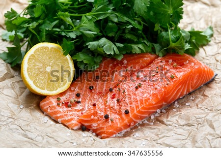 Raw Salmon fish fillet with fresh herbs on crumpled paper. - stock photo