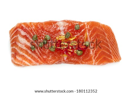 Raw salmon isolated on white.  Garnished with lemon zest, chili and capers. - stock photo