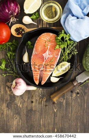 Raw salmon steak in an iron skillet with ingredients for healthy dinner. Top view - stock photo