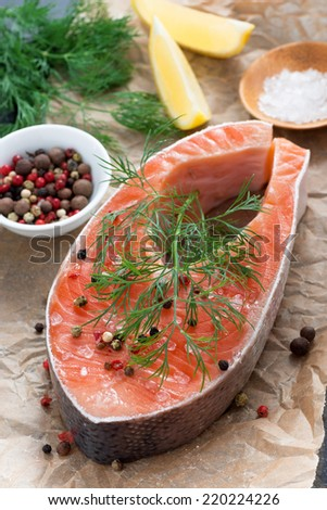 raw salmon steak, lemon and spices prepared for cooking, vertical, close-up - stock photo