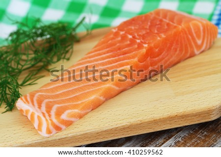 Raw salmon steak on wooden board with fresh dill