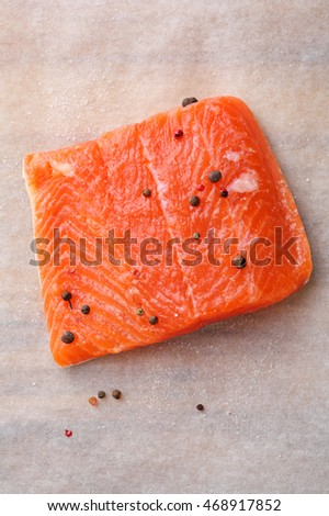 Raw salmon steak with pepper on paper, cooking ingredients